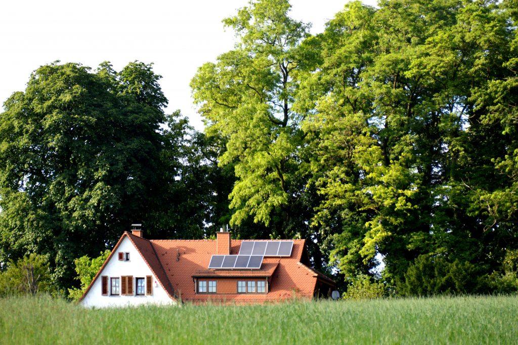 maison écologique dans la nature avec panneaux photovoltaïques sur toit en tuiles